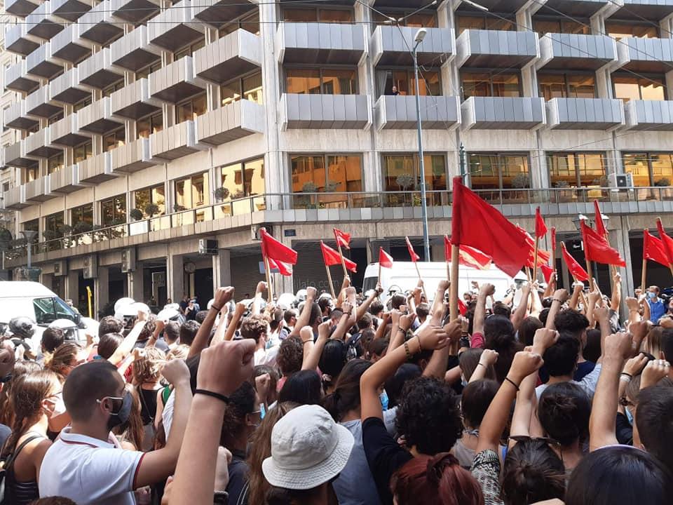 Φοιτητές υψώνοντας τις σημαίες τραγουδούν Μίκη Θεοδωράκη